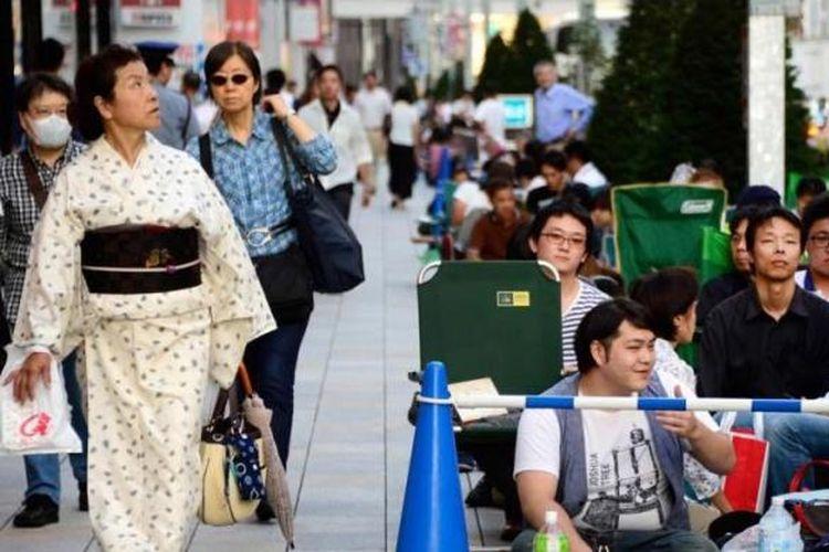 Seorang wanita berkimono berjalan di samping antrean warga di depan Apple Store di Ginza, Tokyo untuk membeli iPhone terbaru, 19 September 2013. Apple resmi memasarkan produk terbaru iPhone 5s dan 5c ke seluruh dunia.