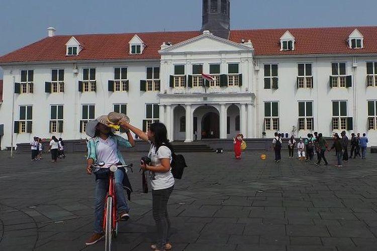 Pengunjung Kota Tua Jakarta sedang menaiki sepeda onthel di pelataran Museum Fatahillah, Jakarta, Selasa (23/6/2015).