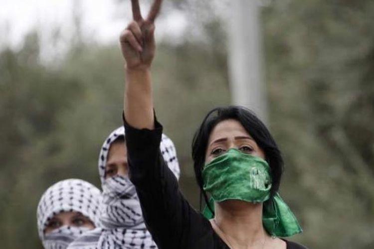 Perempuan Palestina, dengan menutup mulut menggunakan syah Hamas, emngacungkan tanda victory saat bentrokan dengan tentara Israel di Beit El, dekat ramalla, Tepi Barat, 10 Oktober 2015.
