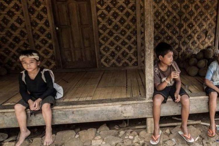 Seorang anak dari suku Baduy dalam (kiri) duduk berdampingan dengan anak-anak dari suku Baduy luar di Kampung Kaduketug, Desa Kanekes, Lebak, Banten, Selasa (1/3/2016). Orang Baduy hari-hari ini sudah mulai tersentuh modernitas dan mengalami perubahan baik dari cara berpakaian hingga memiliki barang-barang modern.(KOMPAS.com / KRISTIANTO PURNOMO)