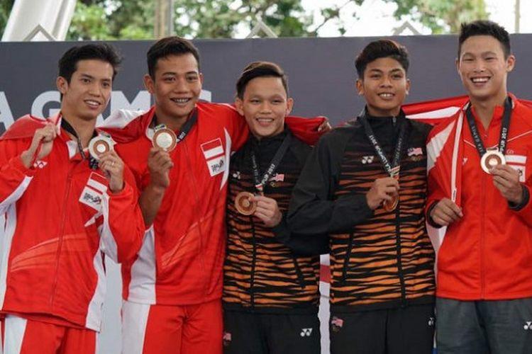 Atlet loncat indah Indonesia, Adityo Restu Putra dan Andriyan (paling kiri) berpose di podium setelah meraih medali perak dari nomor 10 meter papan sinkronisasi SEA Games 2017 yang berlangsung di National Aquatic Stadium, Rabu (30/8/2017).