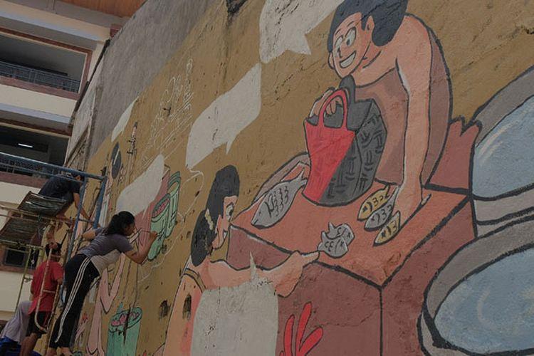 Mahasiswa melukis mural pada tembok Pasar Badung menjelang diresmikan di Denpasar, Bali, Kamis (21/3/2019). Pasar tradisional terbesar di Bali tersebut telah selesai pembangunannya kembali setelah musibah kebakaran dan diresmikan oleh Presiden Joko Widodo, Jumat (22/3/2019).