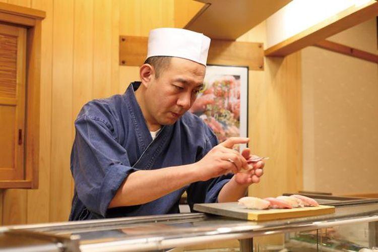 Koki sushi dengan hati-hati menyiapkan setiap hidangan di restoran.