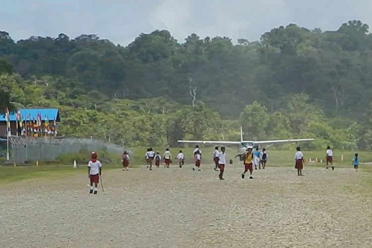 Anak-anak sekolah dasar di landasan pacu Bandara Merdey, Teluk Bintuni, Papua Barat.