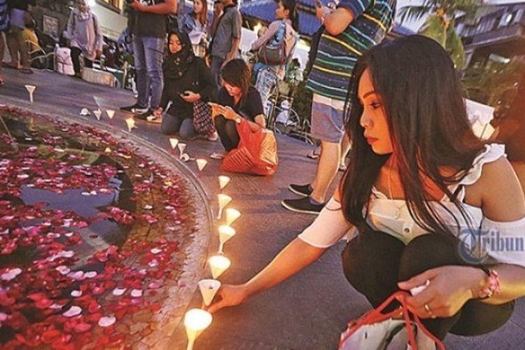 Seorang wisatawan turut menyalakan lilin dalam upacara peringatan 15 Tahun Bom Bali sekaligus launching buku Luka Bom Bali: Kisah Nyata dari Kejadian Bom di Bali di areal Ground Zero Kuta, Badung, Kamis (12/10/2017).