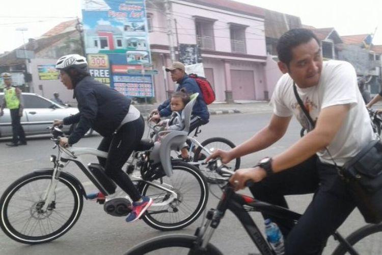 Menteri Susi (kiri) bersepeda sambil membonceng cucunya berkeliling Kota Tegal, Jumat (2/2/2018) pagi.