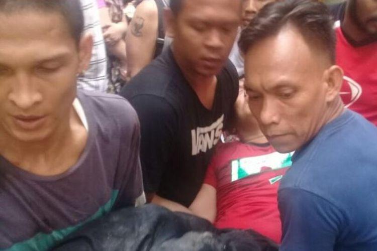 Bripka Eric Tambunan digotong warga setelah dikeroyok di Kampung Kubur, Medan, Sumatera Utara, Sabtu (14/4/2018).