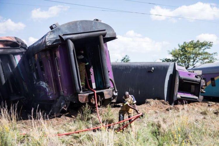 Seorang petugas pemadam kebakaran menarik selang di samping gerbong kereta terguling, setelah terjadi kecelakaan di dekat Kroonstad di provinsi Free State, Afrika Selatan, Kamis (4/1/2018). (AFP via VOA)