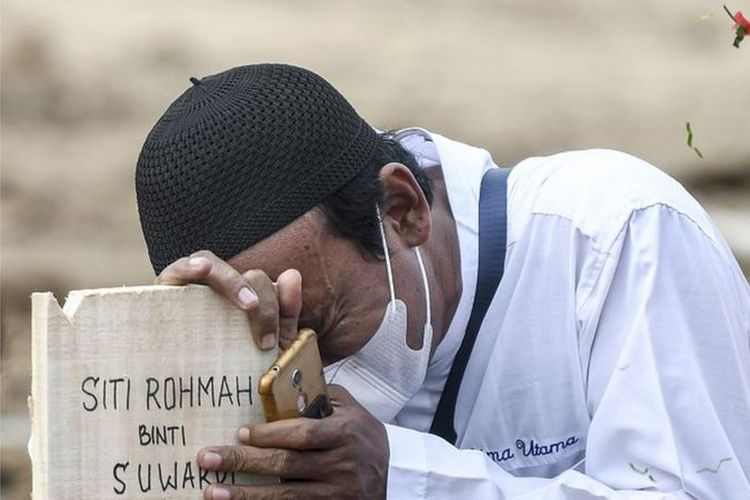 Warga menangis di atas nisan keluarganya di area pemakaman khusus COVID-19 di TPU Rorotan, Cilincing, Jakarta Utara, Senin (28/6/2021).