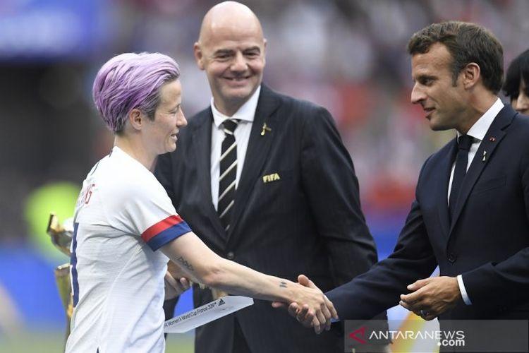 Presiden Prancis Emmanuel Macron (kanan) menyalami kapten tim nasional putri Amerika Serikat Megan Rapinoe (kiri) disaksikan Presiden FIFA Gianni Infantino (tengah) dalam seremoni pengalungan medali dan trofi juara Piala Dunia 2019 yang diraih AS seusai mengalahkan Belanda 2-0 dalam partai final di Stadion Groupama, Lyon, Prancis, Minggu (7/7/2019).