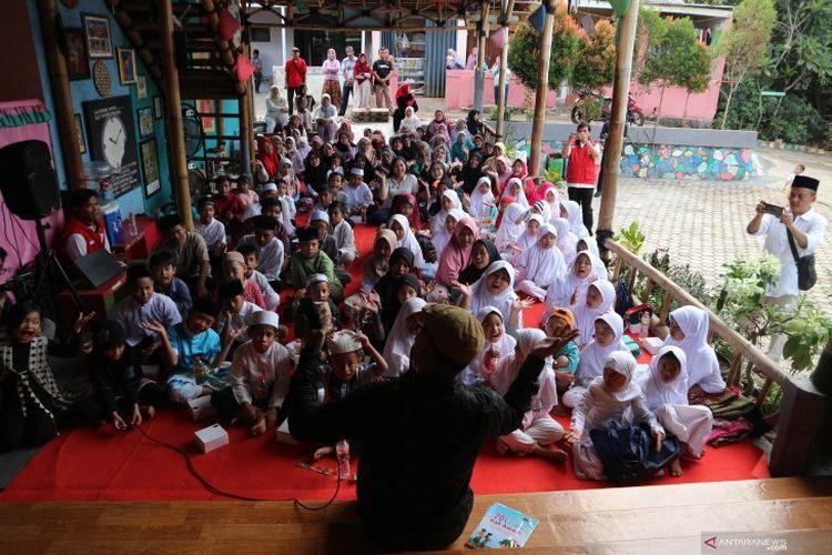 Kak Awam di tengah anak-anak yang semangat menyimak dongengnya pada acara Kampung Dongeng Peduli, Sabtu (23/3/2019) di Ciputat, Tangerang Selatan.