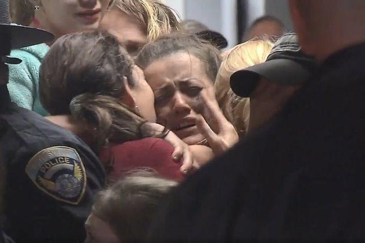 Kayla Williams menangis saat dipeluk oleh seorang kerabat usai dievakuasi dari sebuah tambang. Dia bersama dengan dua orang lainnya terjebak di bawah tanah sebuah tambang batu bara di West Virginia, Amerika Serikat. (ABC News via Daily Mail).