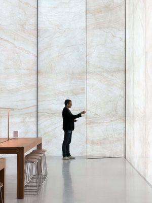 Seorang pengunjung berdiri di depan panel batu kaca di dalam gedung Apple Cotai Store Macau.