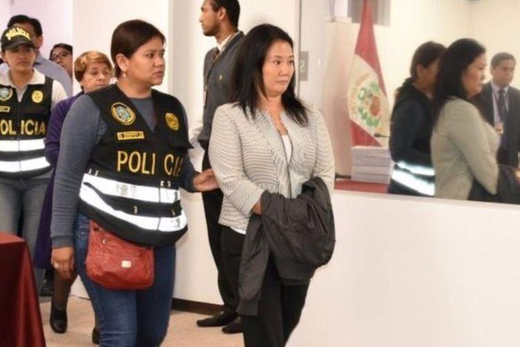 Keiko Fujimori, pemimpin oposisi dan putri mantan presiden Peru Alberto Fujimori, dikawal oleh petugas polisi di kantor Kehakiman, di Lima. Dia ditangkap pada Rabu (10/10/2018) karena dugaan pencucian uang yang melibatkan raksasa konstruksi Brasil, Odebrecht. (AFP/Juan Carlos VIVAS/ Peruvian Judiciary)