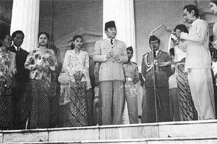 Soekarno di depan Istana Merdeka menyimak seorang aktor film membaca puisi (1956).