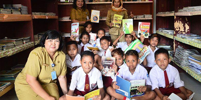Beberapa siswa-siswi dan guru serta kepala sekolah SDN 48 Manado tengah berfoto bersama di perpustakaan kecil sekolah, Senin (24/7/2017) siang. Sekolah ini memiliki pojok bacaan di setiap kelas. Di sini para guru menanamkan rasa malu kepada para siswanya jika tidak membaca buku.