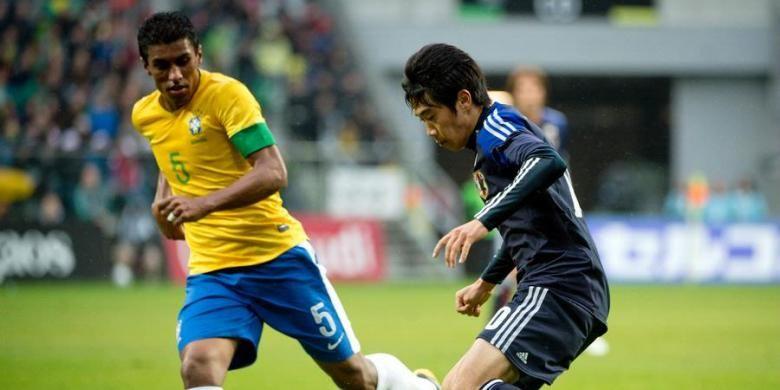Gelandang Brasil, Paulinho (kiri), tengah memperhatikan penyerang Jepang, Shinji Kagawa, dalam laga uji coba di Stadion Municipal, Wroclaw, Polandia, Selasa (16/10/2012). Brasil akhirnya menang 4-0.