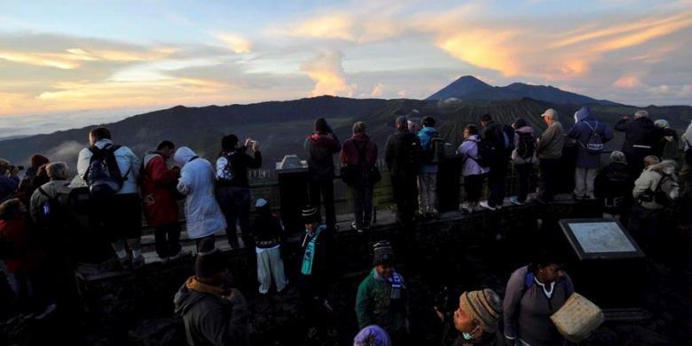 Wisatawan menikmati keindahan pagi kawasan Gunung Bromo dari atas Gunung Penanjakan, Pasuruan, Jawa Timur, Selasa (23/4/2013). Gunung Bromo masih menjadi tujuan wisata utama di Jawa Timur dengan jumlah pengunjung rata-rata 10.000 orang per bulan.