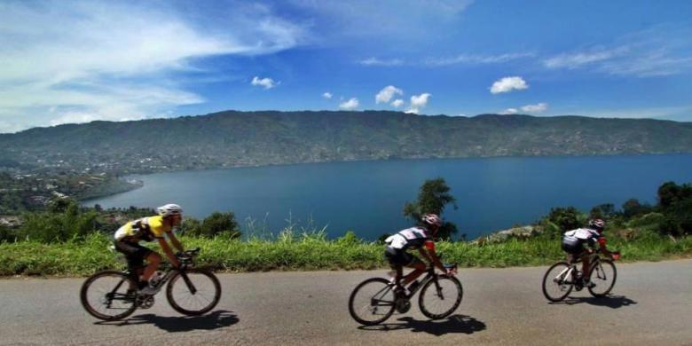 Pebalap sepeda Tour de Singkarak 2013 memacu sepedanya melewati Danau Kembar, Solok, Sumatera Barat, Kamis (6/6/2013). Etape 5 balap sepeda Tour de Singkarak 2013 Sawahlunto - Muara Labuh menempuh jarak 138,5 km dengan juara 1 Amir Kolahdozhagh dari tim TPT.