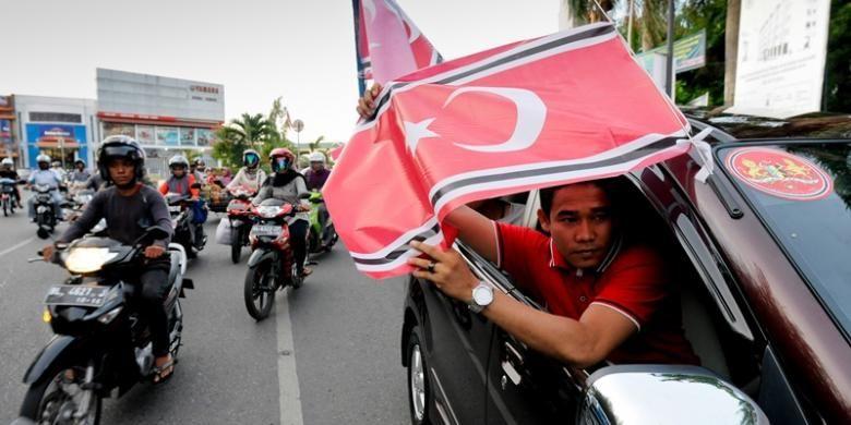 Warga dari Kabupaten Nagan Raya konvoi sambil mengibarkan Bendera Bintang Bulan di seputaran Kota Banda Aceh, Selasa (26/3/2013). Sejak 25 Maret 2013, Pemerintah Aceh telah menetapkan dan mengundangkan dalam lembaran daerah bendera dan lambang Gerakan Aceh Merdeka (GAM) sebagai lambang dan bendera daerah.