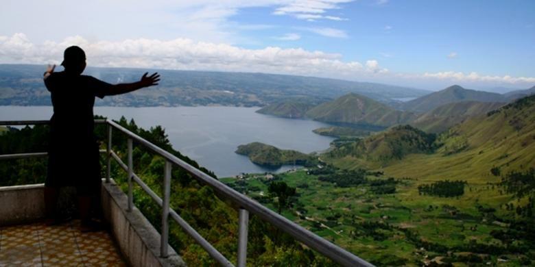 Wisatawan domestik di Menara Pandang Tele melihat panorama Danau Toba dari ketinggian. Menara ini berada di Kabupaten Samosir, Sumatera Utara,