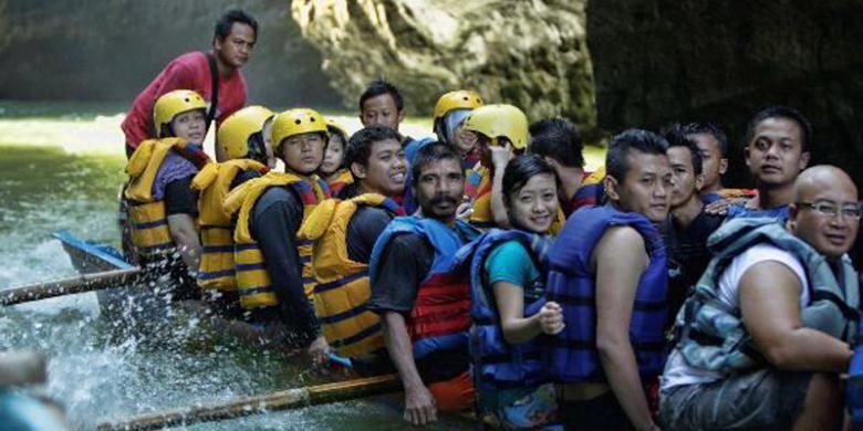 Wisatawan menggunakan perahu saat mengunjungi Green Canyon, Cijulang, Pangandaran, Jawa Barat, Sabtu (4/5/2013). Objek wisata ini menawarkan keindahan dinding bebatuan yang ditutupi lumut dan wisatawan dapan menikmatinya dengan menyusuri sungai menggunakan perahu.