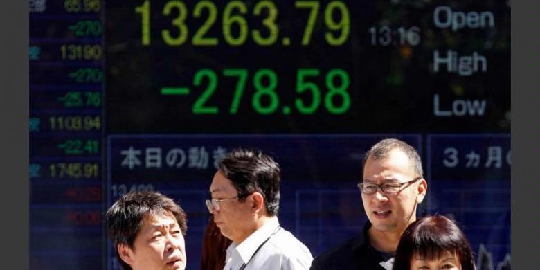 Pejalan kaki menunggu untuk menyeberang di depan papan indeks Nikkei 225.