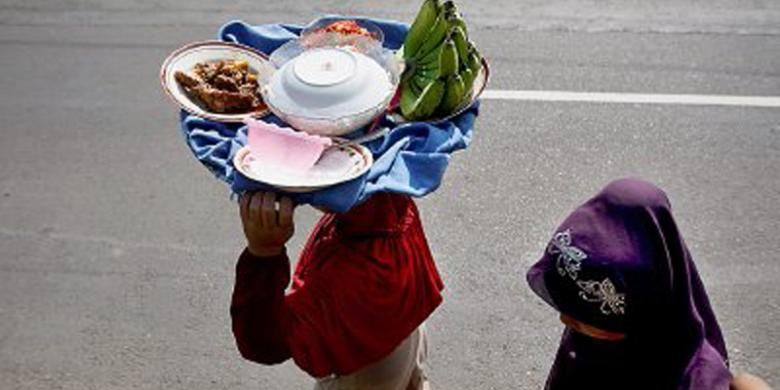 Ibu-ibu membawa antaran makanan di Jalan Raya Payakumbuh-Lintau, Sumatera Barat, Senin (8/7/2013). Rendang menjadi bagian penting di antara sejumlah makanan yang dibawa. Antaran makanan ini dibawa dan dimasak ibu-ibu untuk acara mendoa (berdoa bersama dan siraman rohani) di masjid terdekat untuk menyambut bulan puasa.