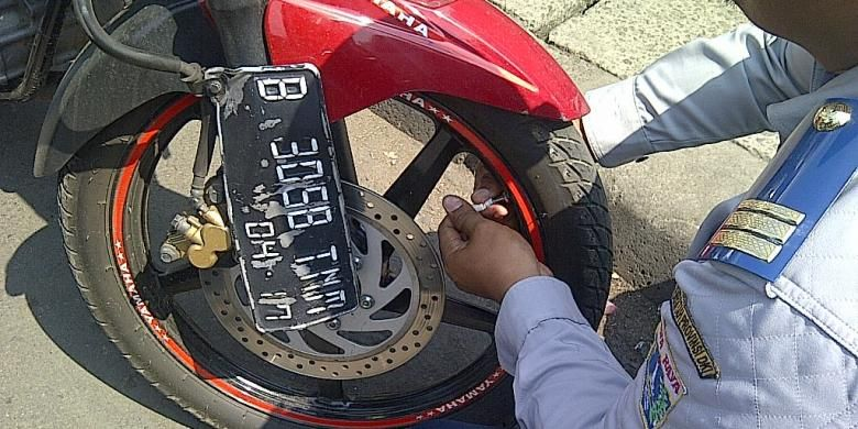 Petugas Sudinhub Jakarta Timur mencabut pentil motor yang parkir di bahu jalan di depan Stasiun Jatinegara, Jakarta Timur, Senin (23/9/2013). Hal tersebut dilakukan untuk mengurangi kemacetan yang sering terjadi di kawasan Jatinegara.