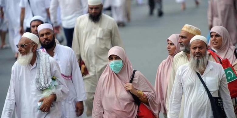 Umat Islam mengenakan masker ketika menuju Masjidil Haram, Kota Mekkah, Arab Saudi, 8 Oktober 2013. Lebih dari dua juta muslim tiba di kota suci ini untuk ibadah haji tahunan.