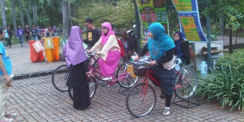 Pengunjung tengah mencoba sepeda yang bisa mencharge telepon genggam di Festival taman di Taman Cattleya, Tomang, Jakarta Barat, Sabtu (19/10/2013).