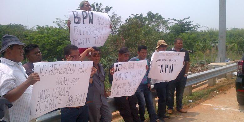 Sejumlah warga Petukangan Utara yang terkena dampak dari pembangunan proyek Jakarta Outer Ring Road West 2 (JORR W2) saat menggelar aksi unjuk rasa di tengah proyek Jalan tol KM 12 JORR W2, Petukangan Utara, Pesanggrahan, Jakarta Selatan, Rabu (23/10/2013). Mereka menuntut Badan Pertanahan Nasional (BPN) Jakarta Selatan yang salah mengukur denah tanah milik mereka