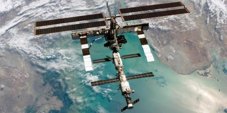 Foto utuh Stasiun Luar Angkasa Internasional saat berada di orbit bumi di atas Laut Kaspia. Di dalam inilah para awak Ekpedisi 35 berada untuk melakukan penelitian luar angkasa.