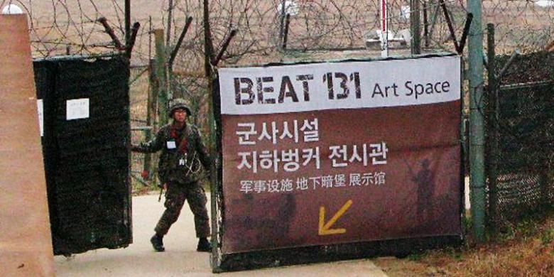 Seorang prajurit Korea Selatan membuka pintu gerbang menuju salah satu pos pemantauan militer di dekat zona demiliterisasi (DMZ) dan perbatasan Korsel dengan negeri tetangga musuh bebuyutannya, Korea Utara, Rabu (6/11/2013). Kawasan DMZ itu telah menjadi salah satu tujuan wisata yang banyak dikunjungi turis, terutama wisatawan asing.