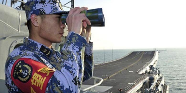 Seorang pelaut China sedang memantau situasi dari atas geladak kapal induk Liaoning dalam sebuah latihan pada Nomber lalu di Laut China Selatan.