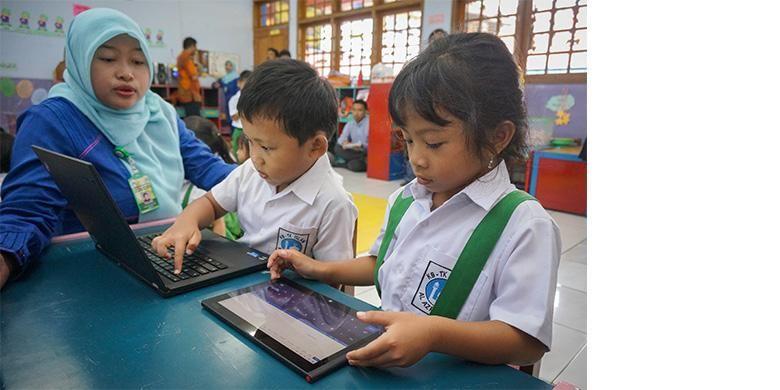 Nura Uma Annisa, guru komputer TK Islam Al-Azhar 22 Semarang, mendampingi anak muridnya dalam menggunakan tablet dan laptop untuk belajar, Selasa (17/12/2013)