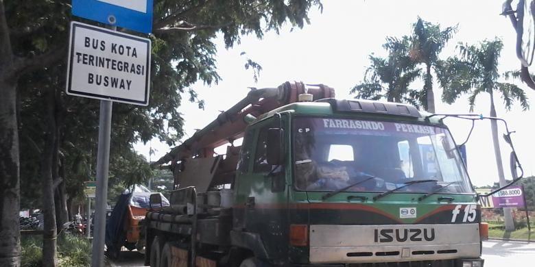 Tempat pemberhentian bus kota terintegrasi busway (BKTB) dimanfaatkan sopir truk di kawasan proyek Pantai Indah Kapuk Mall menjadi tempat parkir, Kamis (13/2/2014).