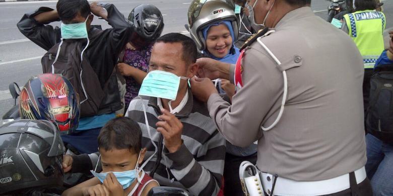 Polisi membagikan masker kepada pengendara sepeda motor di Kota Surabaya, Jumat (14/2/2014). Abu vulkanik akibat letusan Gunung Kelud juga mengguyur Kota Surabaya.