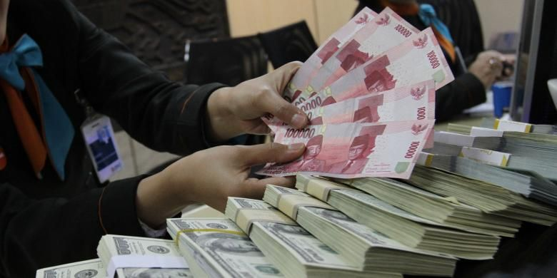 Teller sebuah bank di Jakarta Selatan menghitung uang rupiah di atas dolar Amerika Serikat.