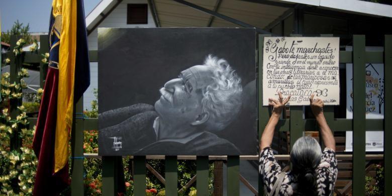 Seorang perempuan, Jumat (18/4/2014), menempelkan pengumuman di samping gambar wajah Gabriel Garcia Marquez, penulis dan penerima Nobel Sastra 1982, yang meninggal pada Kamis (17/4/2014) dalam usia 87 tahun.