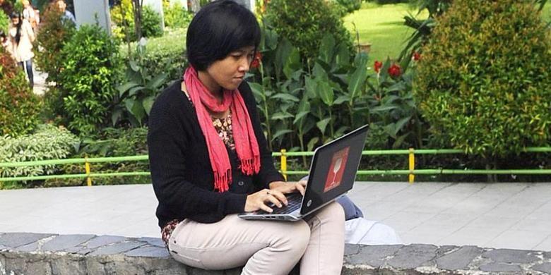 Warga menggunakan fasilitas hot spot gratis di Taman Bungkul, Surabaya, Minggu (25/5/2014). Taman yang menjadi ikon Kota Surabaya tersebut tidak hanya sebagai kawasan terbuka hijau, tetapi juga menjadi tempat bertemunya sejumlah komunitas kreatif.