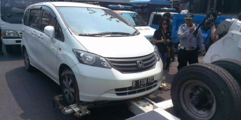 Petugas Dishub DKI menderek mobil yang parkir sembarangan di kawasan Tanah Abang, Jakarta Pusat, Senin (8/9/2014).
