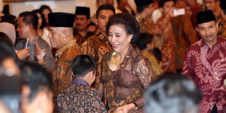 Menteri Kelautan dan Perikanan Susi Pudjiastuti berbicara dengan cucunya sebelum melakukan sumpah jabatan menteri di Istana Negara, Jakarta, Senin (27/10/2014).