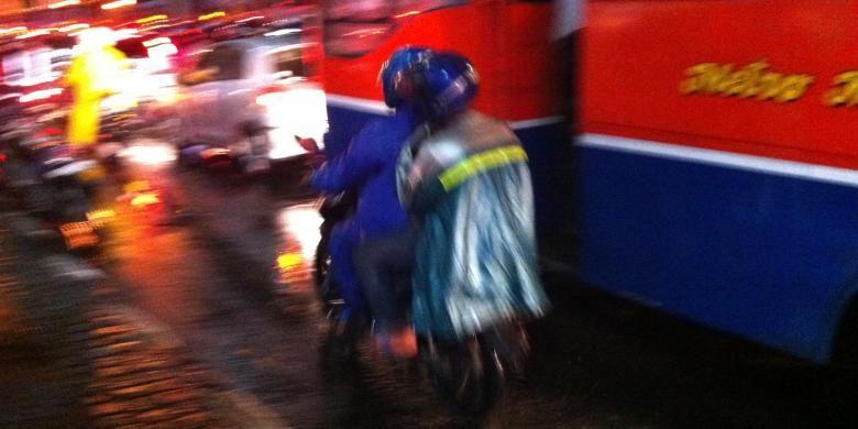Pengendara sepeda motor yang menggunakan jas hujan ponco menutupi lampu rem dan sen.