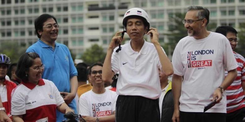 Presiden Joko Widodo mengenakan helm dan disaksikan oleh Duta Besar Inggris untuk Indonesia Moazzam Malik di kawasan Bundaran Hotel Indonesia, Jakarta, Minggu (30/11/2014). Pada acara ini Pemerintah Kota London menyumbangkan 12 unit sepeda ke Pemerintah Provinsi DKI Jakarta.