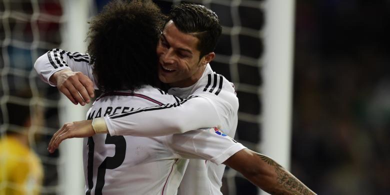 Penyerang Real Madrid, Cristiano Ronaldo (kanan), memeluk Marcelo yang memberikan assist sehingga dia mencetak gol ketiga Madrid saat menang 3-0 atas Celta Vigo dalam lanjutan Primera Division di Santiago Bernabeu, Sabtu (6/12/2014). Ronaldo membuat hat-trick dalam laga ini.
