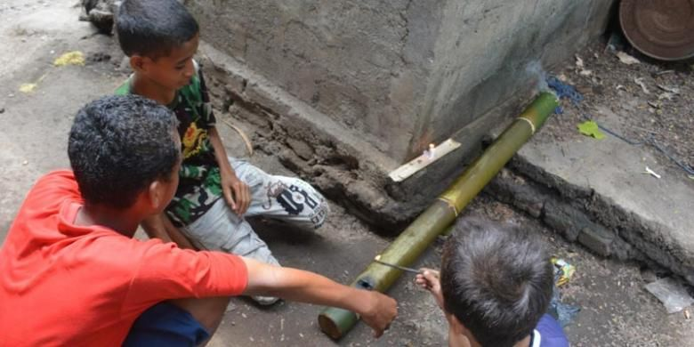 Tiga orang anak sekolah dasar di Kompleks Mabako, Kelurahan Watunggene, Kecamatan Kota Komba, Manggarai Timur, Flores, NTT, Jumat (19/12/2014) membunyikan meriam bambu di samping rumah mereka. Tradisi meriam bambu merupakan warisan leluhur orang Flores untuk menyambut kelahiran Isa Almasih.