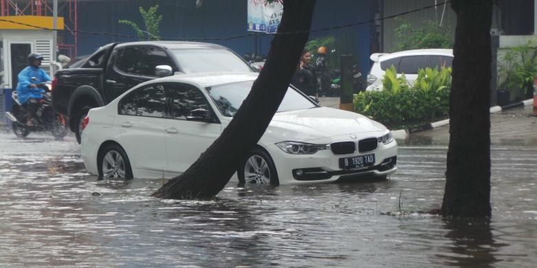 Diduga mogok karena banjir, sedan BMW bernomor polisi B 1920 TAD berwarna putih terjebak di tengah banjir yang menggenangi Jalan Boulevard Barat, Kelapa Gading, Jakarta Utara, Jumat (23/1/2015).