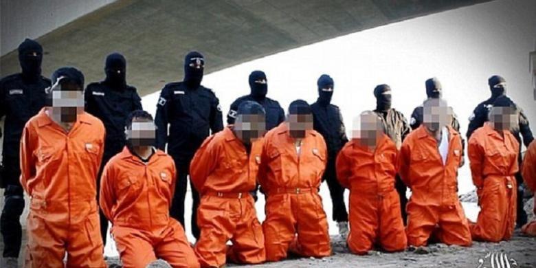 Anggota ISIS, yang berbaju hitam dan berdiri, dengan para tawanan mereka.