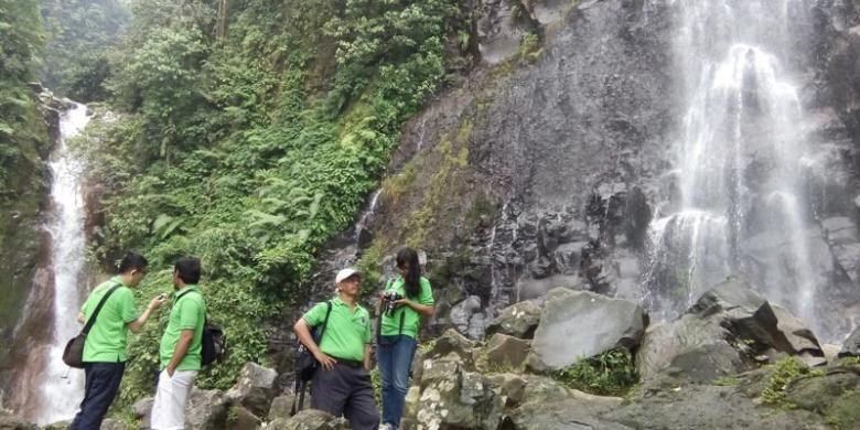 Pengunjung di antara dua air terjun, Curug Cigamea (kiri) dan Curug Cimudal (kanan) di Kawasan Taman Nasional Gunung Halimun Salak (KTNGHS), Kabupaten Bogor, Jawa Barat.